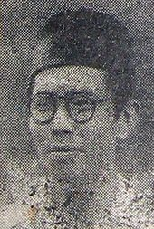 A man in spectacles and a songkok, looking left