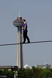 A man with a purple shit and black pants tightrope walks with a large tower in the background