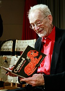 Bridwell in 2011, holding a copy of the first Clifford the Big Red Dog book.