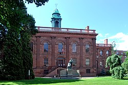 A two-story brown stone building with ornate classical detailing in a park setting. It has a green cupola on top and a green statue of a man in front.