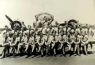 Military personnel standing or seated in front of twin-engined military monoplane