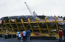 People standing in front of the wreck of the Mary Rose while in its protective cage