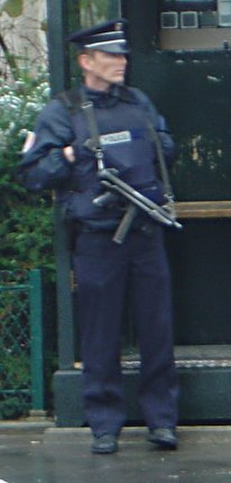 Outline of France - A policeman armed with a submachine gun guarding a police station in Paris