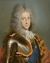 A young man wears a powdered wig while posing in a suit of armour.