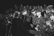 Clinton greeting U.S. troops at Tuzla Air Base in Bosnia while she is walking. This image was taken in December 1997.