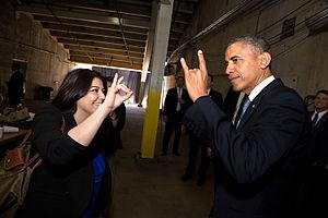 "University of California, Irvine - A UC Irvine alumna shows President Obama how to do the ""Rip 'em Eaters"" hand sign."