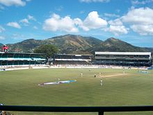 A stadium with people playing cricket. Large mountains are in the background, behind the stands