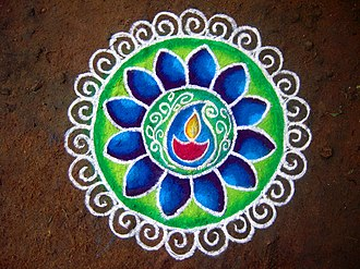 Rangoli or Kolam decorations for Diwali, are prepared from coloured flour (shown), or with flower petals. They are floor decorations near entrances and corridors to welcome goddess Lakshmi and guests.[38] - Diwali