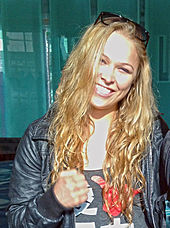 A photograph of a woman with long, blonde hair looking at the viewer while wearing a black leather jacket and smiling all on a very sunny day