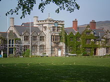 A stone building, partly ivy-covered, seen from a slight angle, with a playing field in the foreground.  The front of the building contains a square battlemented tower, two shaped gables and a series of plain gables.
