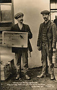 Two miners pose for the camera. One holds a canary in a cage.