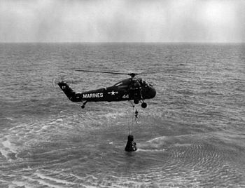English: NASA astronaut Alan B. Shepard Jr. is hoisted up in a body harness by a U.S. Marine Sikorsky UH-34D helicopter recovery team of Marine squadron HMM-262 following the first Project Mercury suborbital space flight, 5 May 1961. Astronaut Shepard, along with his spacecraft, was then taken to the U.S. Navy carrier Lake Champlain (location: 27.23° N 75.88° W).