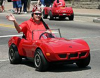 A Shriner in an iconic miniature car participating in a Memorial Day parade