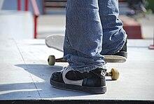 Skateboarder mentre si prepara ad affrontare un giro di prova prima di una competizione (dettaglio).