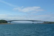 A body of blue water is spanned by a concave bridge of modern design in the middle distance. A small lighthouse can be seen beyond the bridge under its span.