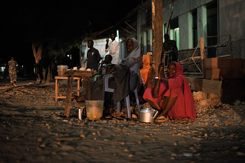 File:Somali women sell tea on the side of the road in Baidoa, while Ethiopian soldiers as part of the African Union Mission in Somalia, conduct a night patrol through the city on June 22. AMISOM Photo - (14517800642).jpg