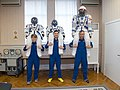 Soyuz MS-11 crew members with their space suits.jpg