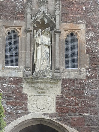 Alphington, Devon - Porch, Church of St Michael and All Angels, with statue of St Michael the Archangel slaying a dragon. Below are displayed the armorials of the Courtenay family, Earls of Devon, sometime lords of the manor, worn away with only the supporters of a boar (dexter)and dolphin (sinister) still visible
