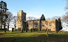 A stone church seen from a slight angle, with an embattled tower on the left, the nave in the centre, and the chancel on the right