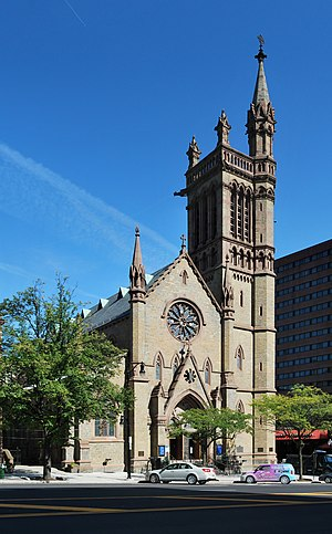 A Gothic stone church with a pointed facade and a tower on the right, with a smaller tower rising from its own right, seen from across a city street