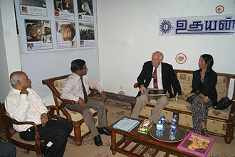 Uthayan - Stephen J. Rapp, the United States Ambassador-at-Large for War Crimes Issues and Michele J. Sison, US ambassador to Sri Lanka are discussing with E. Saravanapavan, Managing Director of the Uthayan newspaper and M. V. Kanamaylnathan, Editor-in-chief  at Uthayan Newspapers's Office in Jaffna on 8 January 2014. Some of the bullet holes and portraits of slain staff are visible on the wall behind them.