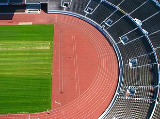 Sport of athletics - A typical track and field stadium with an oval running track and a grassy inner field