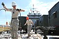 U.S. Army Sgt. Joseph Ferro, left, a watercraft operator with the 481st Transportation Company (Heavy Boat), U.S. Army Reserve, removes latches used to secure cargo on board Landing Craft Utility 2028 at Port 130514-A-AM107-007.jpg