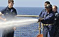 U.S. Navy Ensign Delores Lewis, right, sprays water at a simulated fire as Ensign Alexander White, left, watches during damage control training aboard the amphibious dock landing ship USS Whidbey Island (LSD 41) 110611-N-QP268-491.jpg