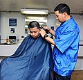 U.S. Navy Ship's Serviceman Seaman Recruit Sam Suprana gives a haircut to Machinist's Mate Fireman Apprentice Luis Plata in the barber shop aboard the aircraft carrier USS George H.W. Bush (CVN 77) in 130523-N-CZ979-050.jpg