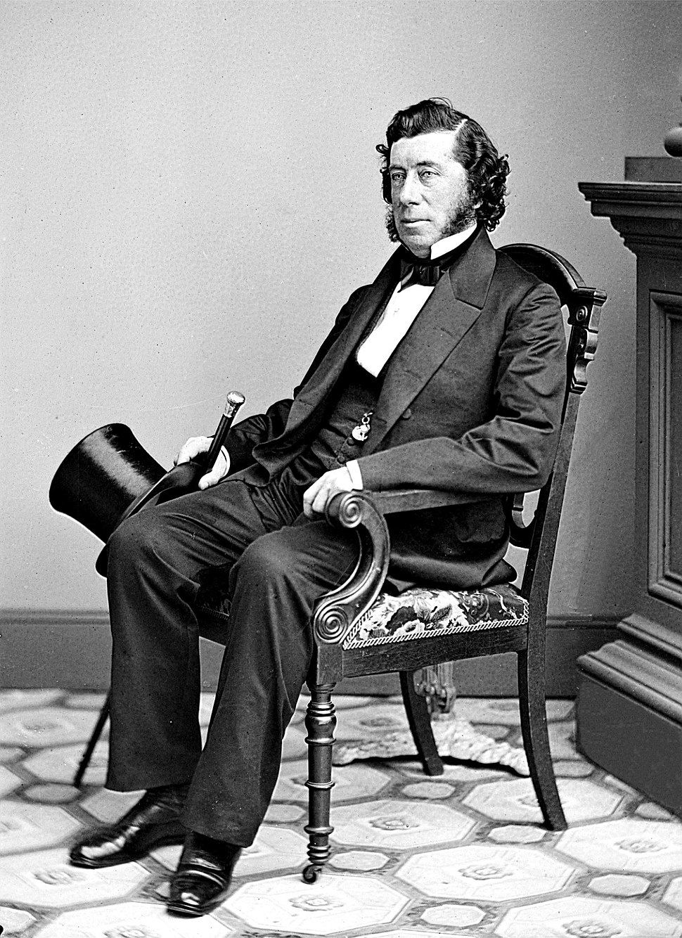 Studio portrait photo of Sen. Hamilton Fish seated position showing head and shoulders with top hat and cane held in right hand.