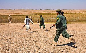 Afghan Local Police - An ALP commander (in white) leads three ALP officers (in dark green) towards the sound of machine gun fire