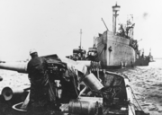 A photograph of two ships. In the foreground is the open bow of USS Rambler with an anti-submarine gun mounted to the left of the frame. USS Bridgeport is in the background of the photo with the bow pointing towards Rambler. There are four smaller ships beside Bridgeport, two on each side.