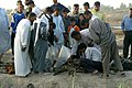 US Navy 030507-M-5882G-042 Iraqi citizens examine human remains found at mass gravesites near a farm on the outskirts of Al Mahawil.jpg