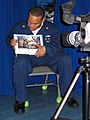 US Navy 041015-N-0000C-001 Operations Specialist 2nd Class Marvell A. Gillespie reads a bedtime story to his kids via video.jpg