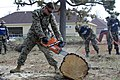 US Navy 050909-N-1467R-077 A U.S. Marine assigned to 11th Marine Expeditionary Unit (MEU-11) stationed at Camp Pendleton, Calif., cuts a fallen tree as part of the cleaning efforts st D'Iberville Elementary School.jpg