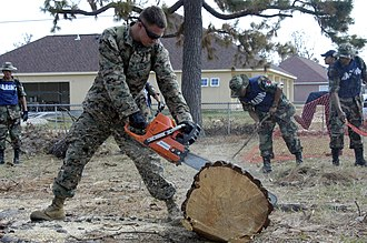 Mexican response to Hurricane Katrina - Mexican marines and U.S. Marines cleaning up hurricane debris outside of a Mississippi elementary school.