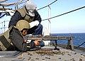 US Navy 060214-N-6616W-001 Gunner's Mate 2nd Class Benjamin Clark, watches as Photographer's Mate 2nd Class Herbert Banks, fires a M-60 machine gun aboard the amphibious assault ship USS Saipan (LHA 2).jpg