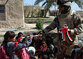 US Navy 060311-N-6901L-172 An Iraqi soldier gives an Iraqi flag to a little girl as her family looks on during a mission to deliver anti-terrorist leaflets and information to local residents on the outskirts of Taji.jpg