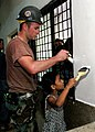 US Navy 060702-N-3714J-101 Navy Builder 2nd Class Shane Murray from Poughkeepsie, N.Y., assigned to Naval Mobile Construction Battalion Four Zero (NMCB-40), receives help from a local girl while painting the pediatric ward at t.jpg
