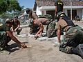 US Navy 060810-N-4689H-002 Engineering Aide Constructoinman Joshua Harvey, Equipment Operator Constructionman John Yarko and Builder Constructionmen Christopher Rinaldi and Jodi Brommer place concrete paving bricks in the court.jpg
