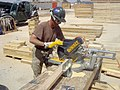 US Navy 070410-N-9456F-002 Builder Constructionman Jeremy Edwards of Corpus Christi, Texas, saws a two-by-four for a Modular Protected Billeting (MPB) facility.jpg
