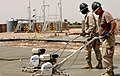 US Navy 070423-N-6436W-024 Seabees from Naval Mobile Construction Battalion (NMCB) 4 and NMCB-28 work together to finish a concrete foundation for a new vehicle maintenance building in Balad, Iraq.jpg