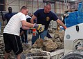 US Navy 071121-N-0577G-005 Sailors stationed aboard the guided-missile destroyer USS Oscar Austin (DDG 79) load debris into a front-end loader to clear space for future construction at a local homeless shelter.jpg