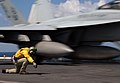 US Navy 071204-N-8923M-156 A shooter gives the final signal as an F-A-18F Super Hornet, attached to the Red Rippers of Strike Fighter Squadron (VFA) 11, launches from the bow aboard the Nimitz-class nuclear-powered aircraft car.jpg