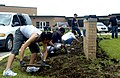 US Navy 080714-N-1232M-250 Volunteers from Naval Station Great Lakes dig up weeds from around the base of the Forrestal School brick sign during a school makeover.jpg