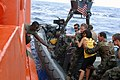 US Navy 090906-N-0120R-120 Members of U.S. Joint Special Operations Task Force-Philippines (JSOTF-P) help an injured woman from an 11-meter rigid hull inflatable boat onto another U.S. Navy vessel.jpg