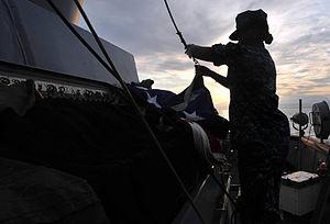US Navy 111231-N-CT127-060 Quartermaster 3rd Class Marshe McNeal prepares to hoist the American flag aboard the San Antonio-class amphibious transp.jpg
