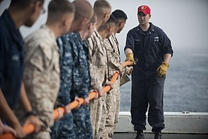 US Navy 120105-N-PB383-003 A Sailor demonstrates how to properly handle a hose during a damage control training exercise.jpg