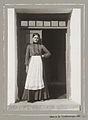 Ung kvinna med förkläde i dörröppning. Bonddotter från Västra Klagstorp, Skåne - Nordiska Museet - NMA.0041078.jpg