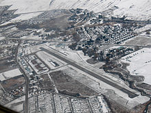 An aerial view of an airport on a snowy day, containing a runway.
